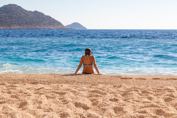 Young woman resting on the beach Kaputash, Turkey