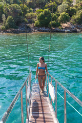 Girl in a swimsuit on the gangway of the ship
