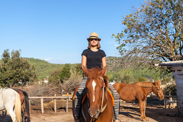 Girl in hat riding on a brown horse