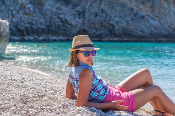 Girl in hat lying on the beach