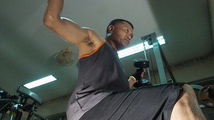 Strong man lifting hand weights in the gym. 60 FPS