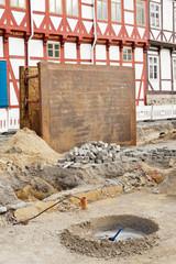 Eine grosse Verbauplatte steht vor einem Fachwerkhaus