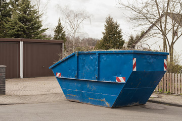 Ein grosser blauer Container für den Frühjahrsputz im Garten