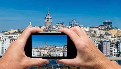 Man and woman hand capturing Beyoglu skyline skyline with smartp
