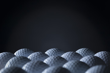 Group of golf balls isolated on black background.