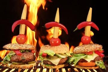Thre Homemade Cheeseburger Close-up On Flaming Barbecue Grill Ba