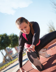 A young female runner stretching her muscles before jogging.