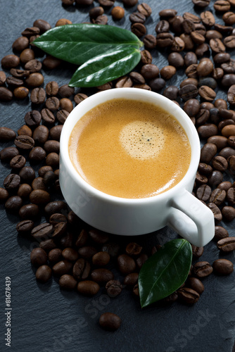 cup of espresso on coffee beans background, top view