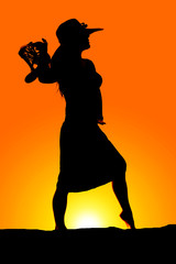 silhouette of a woman in a skirt and hat hold sandles by shoulde
