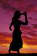 silhouette of a woman in a skirt hand on hat