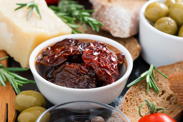 sun-dried tomatoes in a bowl and various appetizers, close-up