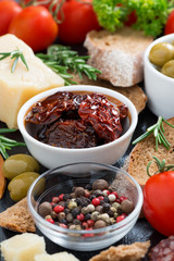 sun-dried tomatoes in a bowl and various appetizers, vertical