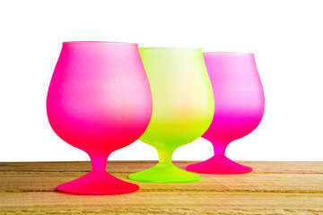 Beautiful three green and pink glasses on wooden table