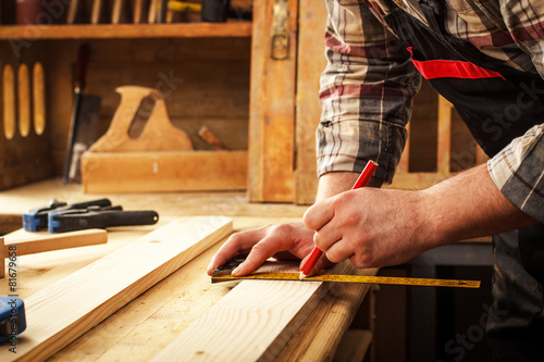 Carpenter marking a measurement on a wooden plank