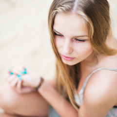Beautiful young girl with bright nails on the beach in summer