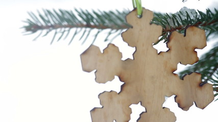 wooden toy in the form of snowflakes hanging on the fir tree