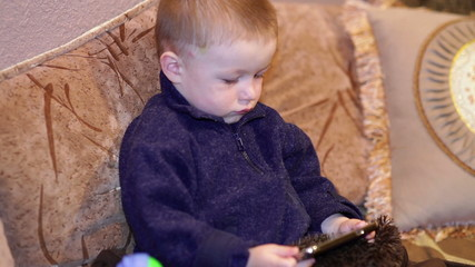 Little boy sitting on the couch and watching a cartoon