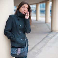 Молодая жизнерадостная девушка разговаривает по телефону.
