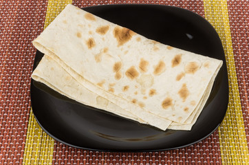 Folded of thin Armenian lavash in glass plate on bamboo mat