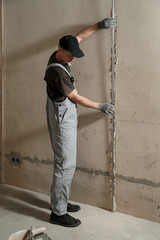 Man fixes a guide to align the walls with stucco