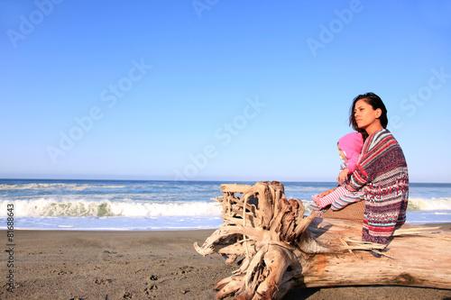 Mutter sitzt mit ihrem Baby am Strand