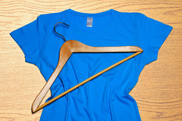 Blue women's t-shirt and wooden hanger lie on wooden background