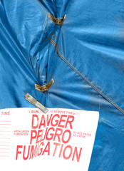 Blue home fumigation tarp, metal spring clamps, and danger sign