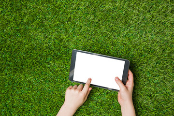 Hand holding tablet pc. over green grass