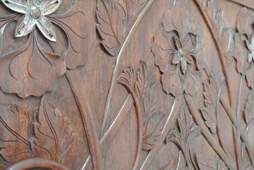 Skilled craftsman adding gold leaf skim to the wood carving