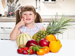 Cute curly little girl eating fresh fruit