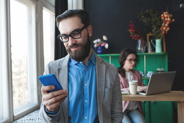 Businessman in glasses with smartphone over woman working on bac