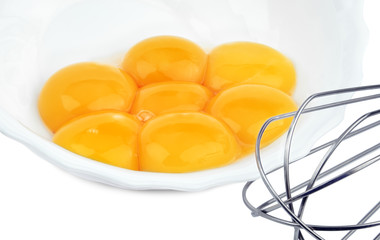 Egg yolks in a plate with a beater isolated on white background.