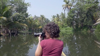 woman photographer exploring kerala backwaters by canoe