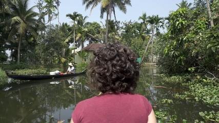 woman exploring kerala backwaters by canoe