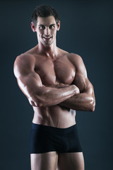 Young shirtless body builder with great smile in black shorts