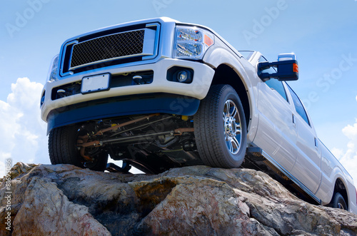 White truck on cliff edge showing undercarriage - 81695086