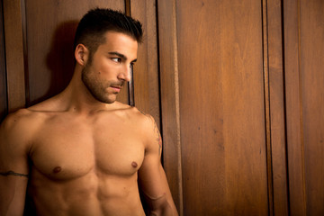 Sexy young man standing shirtless against wooden wardrobe