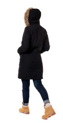 Back view of going  woman in parka.