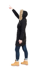 Back view of  pointing young women in parka.