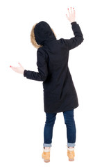 Back view woman in winter jacket  Balances waving his arms.