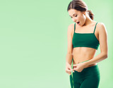 Woman in fitness wear with tape, over green