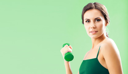 Woman in fitness wear with dumbbell, on green