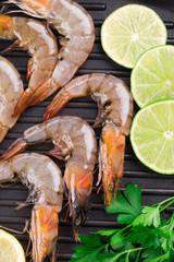 Raw shrimps on black pan.