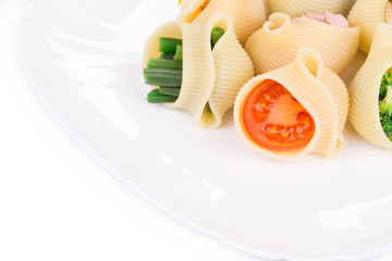 Pasta shells stuffed with vegetables and sausage.