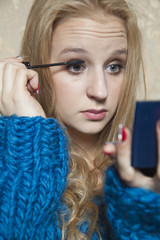 Young beautiful woman doing her makeup with a small mirror