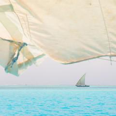 Traditional wooden sailboat sailing on horizon.
