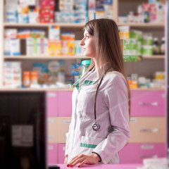 Pharmacist looking away at her working desk
