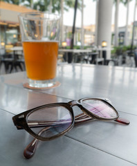 Eyeglasses on a table and background is glass of beer