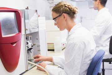 Concentrated scientists working with medical machine