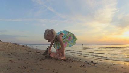 The little girl plays with sand on a beach
